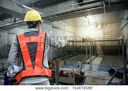 Consulting engineers working with hard hat and holding blueprint in his hand.Construction inspector jobs in the car park building.