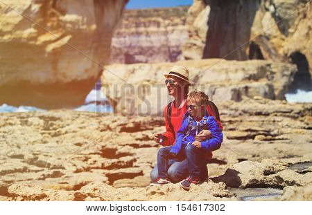 family travel- father and little son taking photos in Gozo island, Malta