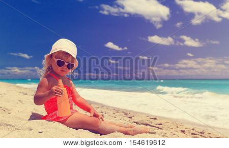 sun protection concept - cute little girl with suncream at beach