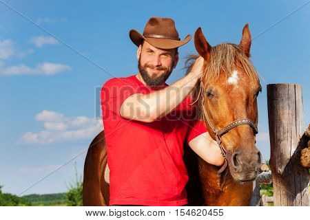 Portrait of smiling cowboy with his bay horse near the enclosure fence in summer