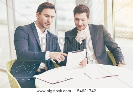 Here the inspiration is. Ambitious handsome professional businessmen making the project and discovering the documents together while using a tablet in their office.