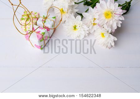 White chrysanthemum flowers with gift boxes on wooden background