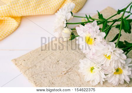 White chrysanthemum flowers with yellow fabric on wooden background
