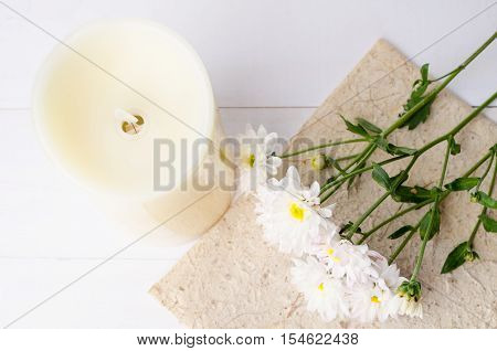 White chrysanthemum flowers with candel on wooden background