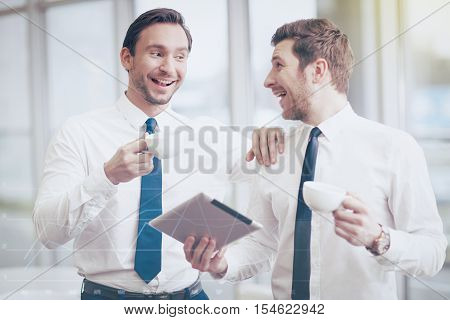 Crack a joke. Two handsome young cheerful businessmen with a tablet laughing and drinking coffee after discussing their work.