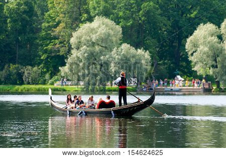 TSARSKOYE SELO, SAINT - PETERSBURG, RUSSIA - JULY 25, 2016: Gondolier and people in the gondola on The Great Pond in The Catherine Park. The Tsarskoye Selo is The State Museum Preserve