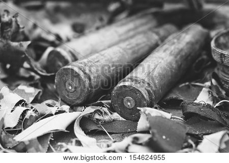 bullet shells from heavy machine gun on the table with camouflage netting black and white photo