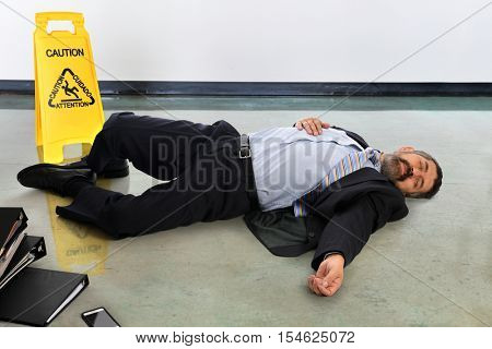 Hispanic businessman laying injured on the floor next to caution sign