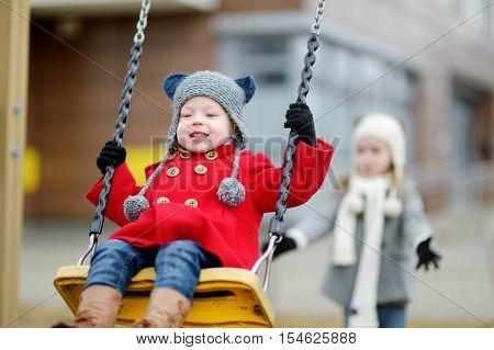 Two Little Sisters Having Fun On A Swing