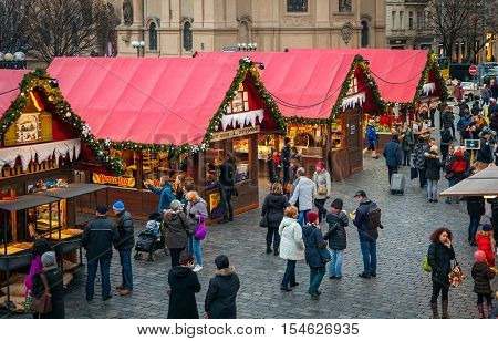 PRAGUE, CZECH REPUBLIC - DECEMBER 11, 2015: Wooden stands offering souvenirs and traditional food during Christmas market taking place each year on December in Old Town Square of Prague..