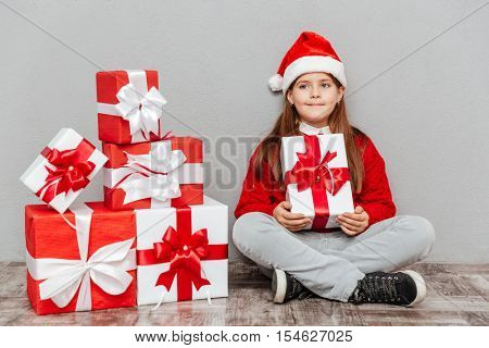 Beautiful little girl in santa claus hat sitting and holding gift box
