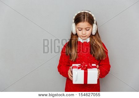 Lovely little girl in red sweater and earmuffs holding present box