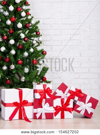 Gift Boxes Under Decorated Christmas Tree With Colorful Balls Over Brick Wall