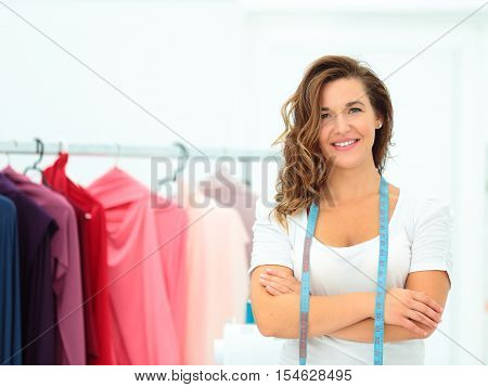 Confident tailor. Beautiful young female tailor holding scissors and smiling at camera while dresses in the background