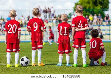 Football soccer match for children. Young boys of football soccer team watching youth football game on sports field. Kids playing summer school football tournament
