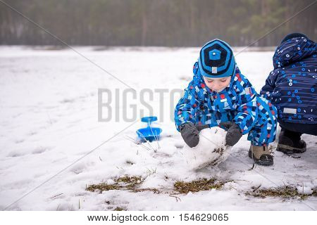 Two Little Siblings Boys Making A Snowman, Playing And Having Fun With Snow, Outdoors On Cold Day. A
