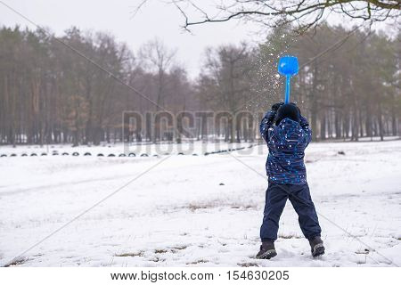 Winter portrait of kid boy in colorful clothes outdoors during snowfall. Active outoors leisure with children in winter on cold snowy days. Happy toddler child having fun with snow in forest.