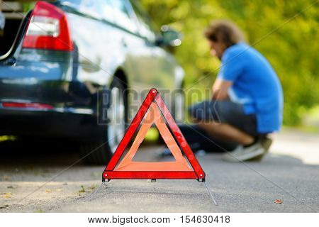 Red warning triangle sign on the road with a man checking his broken car in background
