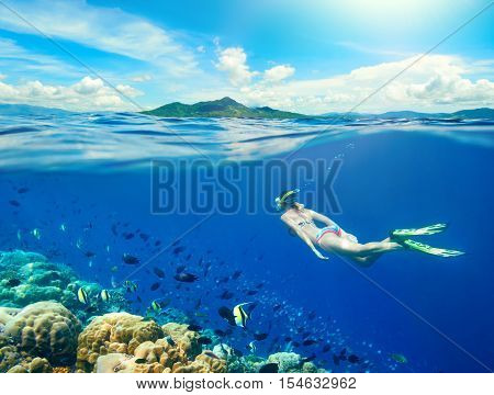 Woman swims around a coral reef surrounded by a multitude of fish on the background Islands. North Sulawesi Indonesia.
