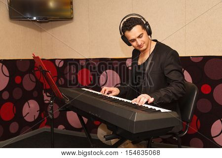 young handsome man playing on a synthesizer