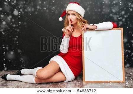 Attracive young woman in santa claus costume with blank white board showing silence sign over black background
