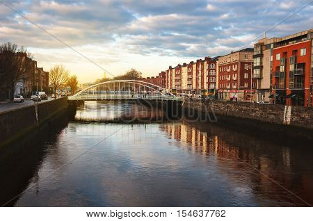 Embankment of Liffey River in Dublin Ireland. Sunset view with buildings and city lights at the background