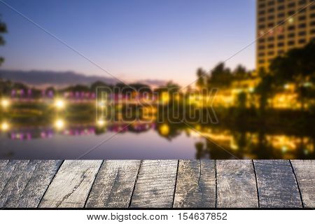 Empty of wood desk form and bokeh light of night city scape background for product presentation display montage.