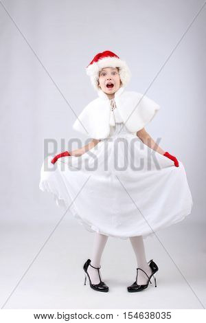 Surprised little girl in Christmas dress, Santa helper hat and big mother`s shoes over light background