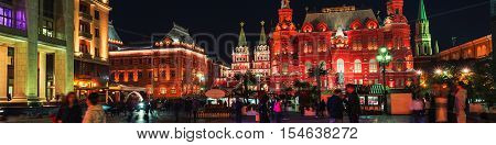 Iverskaya Chapel and State Historical Museum at Manezhnaya square in Moscow, Russia. Night view with famous historical illuminated buildings, and people