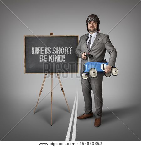 Life is short be kind text on blackboard with businessman and toy car