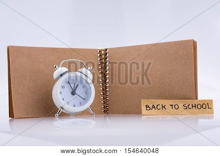 Brown Color Notebook And Alarm Clock