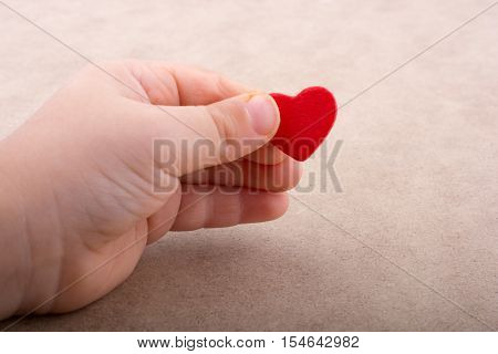 Little red color heart shape in hand on light brown background