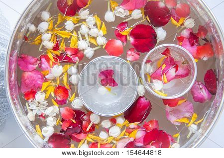 Water with jasmine and roses corolla in bowl for Songkran festival in Thailand.