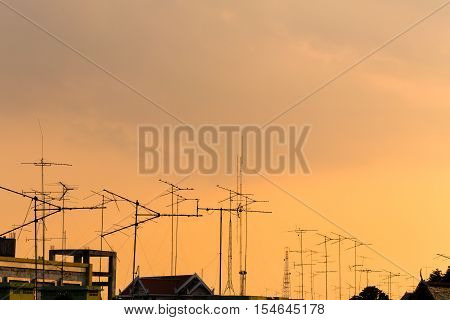 Silhouette, Telecommunication Towers With Tv Antennas And Satellite Dish In Sunset. Many Home Tv Ant