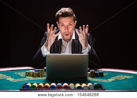Online poker players sitting at the table. He plays on laptop. he won and is happy, and fool. success