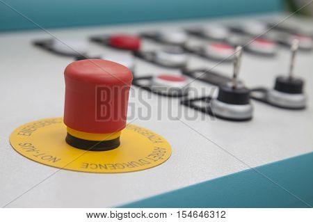 A red emergency panic button with two protection keys next to in the background.