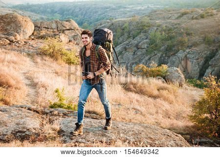 Happy hiker man walking through the valley. Adventure concept