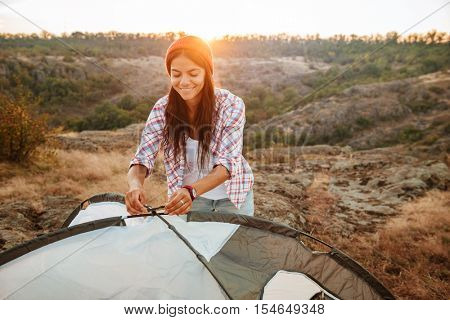 Young happy caucasian woman setting up a tent outdoors