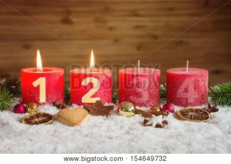 Two Advent Candles Lit In Snow