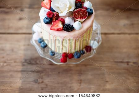 Cake on glass cakestand decorated with various berries, figs, meringues and white rose on top. Studio shot. Wooden background.