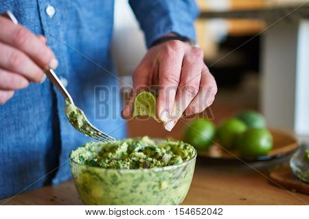 adding lime juice to guacamole