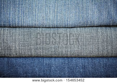 Stack of denim jeans texture or denim jeans background. Old grunge vintage denim jeans. Stitched texture denim jeans background of fashion jeans design.
