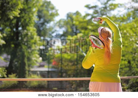 Thick woman makes selfie with racket on tennis playground outdoor, back view
