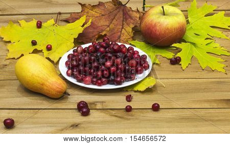 On a wooden surface lie autumn leaves with a pear and an apple and is white plate with cranberries.