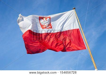 Polish national flag in the blue sky.