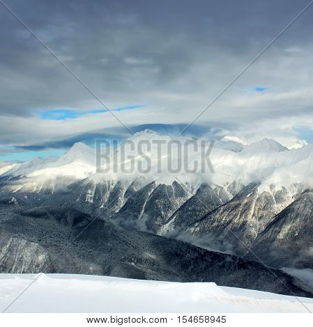 Winter landscape, hight mountains and storm clouds