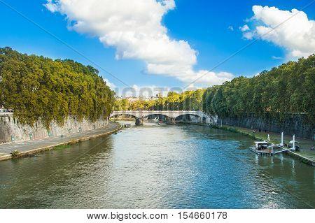 Old stone bridge over Tiber river in Rome, Italy