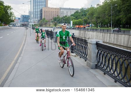 Man, woman and girl in green ride bicycle on street near river at summer day