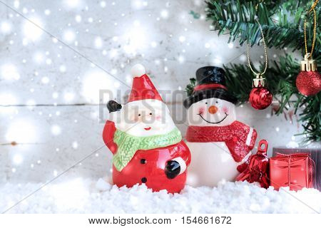Santa Claus with snowman and snowfall over fir tree on vintage wooden background in christmas day with copy space for season greeting and happy new year
