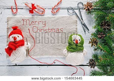 Christmas frame of evergreen twigs with toy snowmen holding needle to stitsh linen napkin with text 'Merry Christmas'. Overhead view
